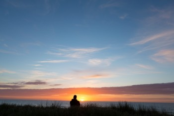 Andy Sutherland watches the sunrise on the beach at Okitu, Gisborne, Eastland, New Zealand
